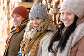 Three young people winter fashion wooden logs