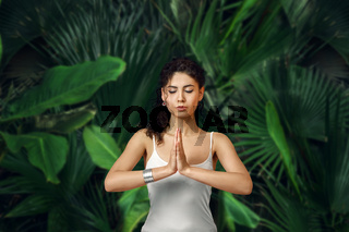 Female meditating in tropical rainforest. Beautiful young woman practicing Yoga outdoor with tropical forest in background