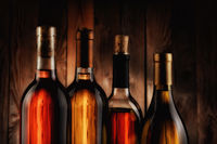 Four wine bottles against a wood background. The bottles have no label and the texture of the backgr
