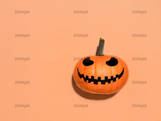 Halloween pumpkin in hand on orange background.