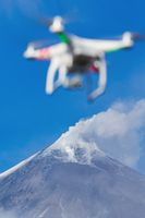 Flying UAV drone quadcopter aerial photography in sky on background volcano eruption
