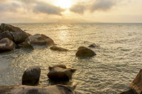 Sunset through the rocks in summer from Ilhabela Island
