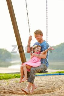 Vater und Tochter schaukeln gemeinsam