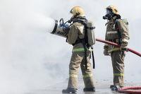 Two firefighters extinguish fire from fire hose, using firefighting water-foam barrel