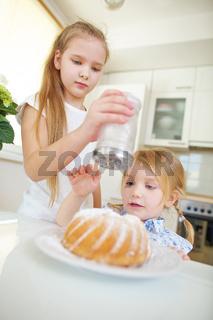 Kinder backen Kuchen und dekorieren mit Puderzucker