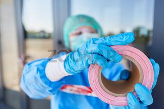 Klinikpersonal sperrt Eingang von Klinik mit Absperrband ab zur Quarantäne