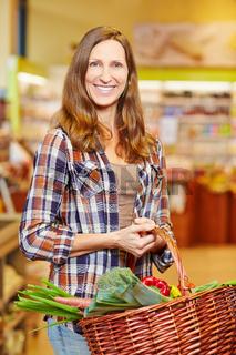 Frau trägt Korb mit Gemüse im Supermarkt