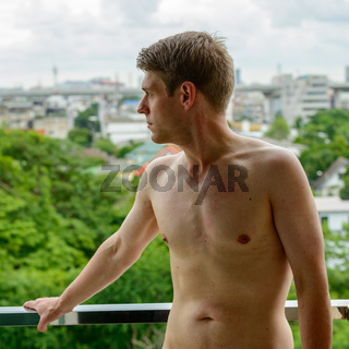 Young handsome shirtless man against view of the city with nature