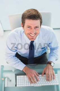 Smiling businessman using his computer