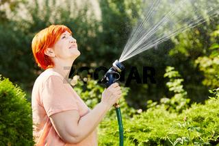 Frau im Garten beim Pflanzen gießen
