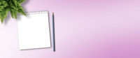 notepad and pencil for taking notes on pink desk