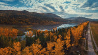 Aerial view of road in beautiful autumn Altai forest