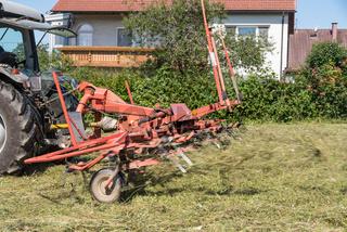 Gemähtes Gras wird von Bauer mit Schwader für Heuernte gewendet - Heuwender