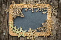 Gold Christmas tree decorations on vintage wooden blackboard