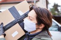 Lieferservice Paketbotin mit Mundschutz trägt Paket zur aus