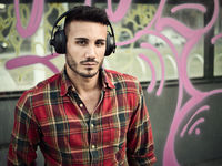 Young attractive man in city listening to music with headphones, sitting on bench