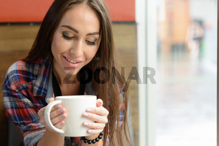 Portrait of young beautiful hipster woman at the coffee shop