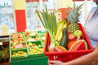 Frau hält Warenkorb in Supermarkt