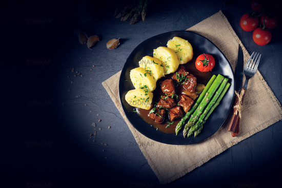 dumplings with beef goulash and green asparagus