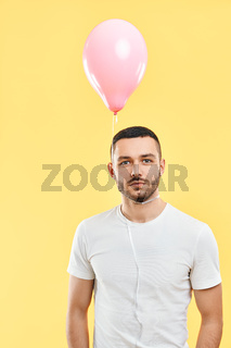 Weird young man with pink air balloon on his neck over yellow background