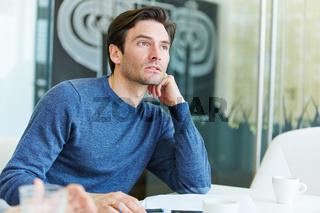 Mann beim Nachdenken am Schreibtisch