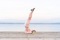 A beautiful woman performs the exercises lifting her legs to the top, lake, pier, Fitness. Sport. Yoga.