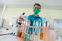 Boy wearing face mask and protective glasses using pipette and test tubes in laboratory