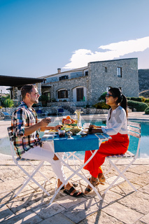breakfast by the pool with a view over the hills and the ocean of Sicily