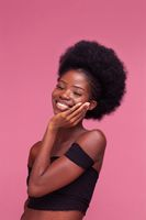Charming Afro American girl smiling touching her chick after spa or face treatment. Beauty girl spa treatment isolated on pink background. Beauty concept.