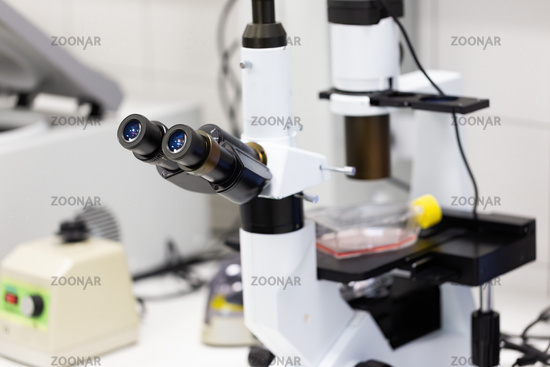 Microscope with two lenses inside medical laboratory