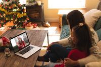 Woman and daughter sitting on couch having a videocall with woman in santa hat waving while holding