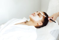 Beautiful relaxed woman having clay face mask in spa salon