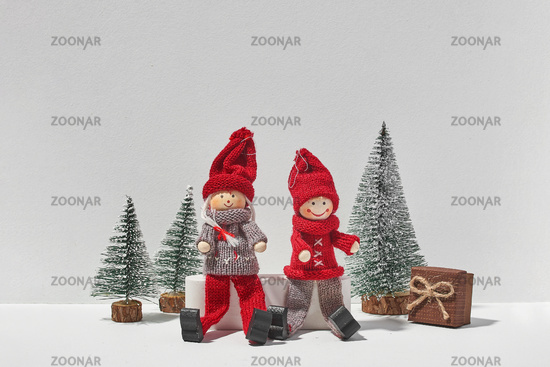 Two christmas elfs sitting together with pine trees and gift on white background. Minimal christmas concept of love