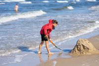 a girl on the beach of Swinoujscie in Poland building a sand castle