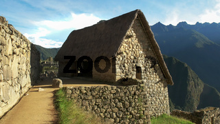 a reconstructed hut at machu picchu on a sunny morning