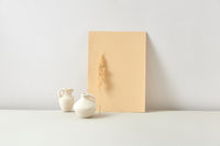 Eco composition from ceramic vases with dry twig and vertical paper sheet.