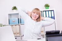 Businesswoman working and stretching her arms behind head indoors at home office. Work, relaxation a