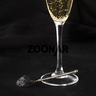 Black caviar and a glass of champagne on a black background with a place for text
