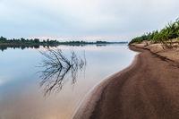 A gentle sandy beach near the river.