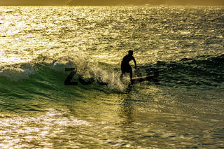 Surfer on the waves of Ipanema beach in sunset