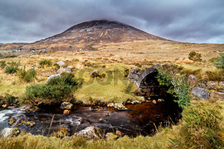 Old small stone bridge over river with view at Errigal mountain