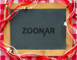 Blackboard blank framed in red Christmas decorations