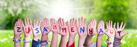 Kids Hands Holding Word Zusammenhalt Means Togetherness, Grass Meadow