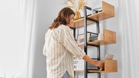 woman arranging books on shelving at home