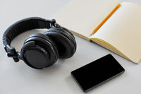 headphones, smartphone and notebook with pencil