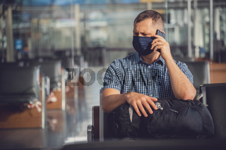 Man with a mask talking on mobile phone in airport lounge