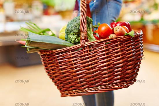 Kunde trägt Einkaufskorb voller Gemüse