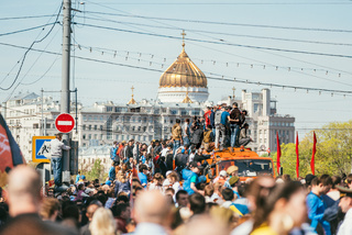 MOSCOW, RUSSIA-MAY 09, 2015: People celebrate Victory Day May 9 in Bol'shoy Moskvoretskiy Most. People climb on an orange truck in the background of the Church of Christ the Savior. A lot of people with the Ribbons of Saint George