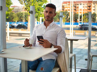 Young Man Drinking Coffee While Looking at Mobile Phone