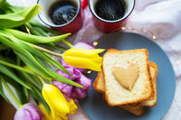 Lovely breakfast in bed. Black coffee, bright flowers, toast with peanut butter. Close-up.